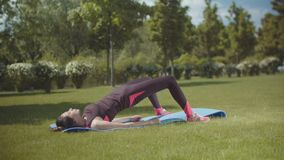 Spory female exercising on fitness mat in park stock video footage