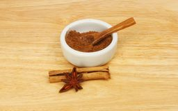 Chinese five spice. In a ramekin with cinnamon and star anise on a wooden chopping board stock image