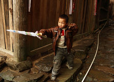 Chinese five year old boy playing with a plastic sword in the village street, editorial images. Royalty Free Stock Photo
