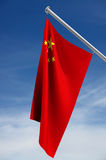 Chinese Flag. Red with yellow stars and hanging from flagpole, against dark blue sky stock illustration