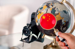 Chinese flag on globe through magnifying Stock Photography