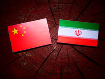 Chinese flag with Iranian flag on a tree stump isolated. Chinese flag with Iranian flag on a tree stump Royalty Free Stock Image