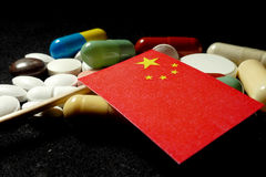 Chinese flag with lot of medical pills isolated on black background Royalty Free Stock Photos