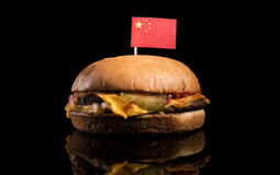 Chinese flag on top of hamburger isolated on black Royalty Free Stock Photos
