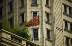 Chinese flags in front of a bank. The flag is in front of a bank in China Stock Images