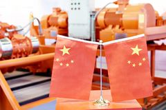 Chinese flags on industrial equipment. Background stock photos