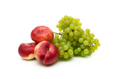 Chinese flat peaches and a bunch of green grapes on white backgr. Ound.  Horizontal photo Royalty Free Stock Images