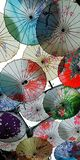 Chinese flower umbrellas make up the sky. royalty free stock photos