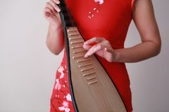 Chinese folk music performer playing Pipa. Chinese folk music performer playing traditional instrument of Pipa at White background.Chinese traditional dress Royalty Free Stock Photos