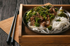 Chinese food - beef prepared with broccoli and rice noodles. Stock Photo
