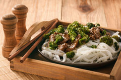 Chinese food - beef prepared with broccoli and rice noodles. Royalty Free Stock Images