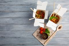 Chinese food in a box on a wooden table. Chinese and Asian fast food. On a gray table is a wooden spoon and cherry tomatoes with spices. Close-up. View from Royalty Free Stock Images