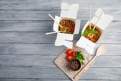 Chinese food in a box on a wooden table. Chinese and Asian fast food. On a gray table is a wooden spoon and cherry tomatoes with spices. Close-up. View from Stock Photo