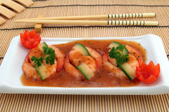 Chinese food - Gourmet broiled king tiger prawns. Chinese food, gourmet tiger king prawns served with a vegetable and tomato garnish with chop sticks on bamboo Stock Image