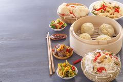 Chinese food on a gray wooden table. Traditional steamed dumplings, noodles, vegetables, seafood. royalty free stock image