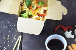 Chinese food, Noodles with pork and vegetables in take-out box on wooden table royalty free stock photo