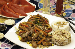 Chinese food. Plate with cninese food, rice, chopped meat and red paprika Stock Photos