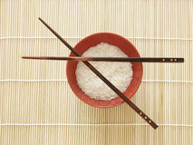 Chinese food - rice bowl. Red bowl of rice and chinese chopsticks, on bamboo background, view from above Stock Photos