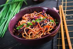 Chinese food. Vegan stir fry noodles with red cabbage and carrot. In a bowl on a black wooden background. Asian cuisine meal stock photography