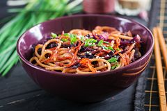 Chinese food. Vegan stir fry noodles with red cabbage and carrot. In a bowl on a black wooden background. Asian cuisine meal stock image
