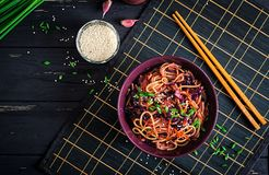 Chinese food. Vegan stir fry noodles with red cabbage and carrot. In a bowl on a black wooden background. Asian cuisine meal. Top view stock photos