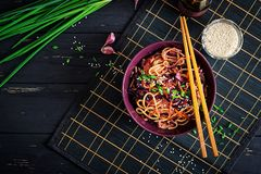 Chinese food. Vegan stir fry noodles with red cabbage and carrot. In a bowl on a black wooden background. Asian cuisine meal. Top view royalty free stock photo