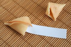 Chinese fortune cookie. Open fortune cookie with a blank slip on a bamboo mat royalty free stock photo