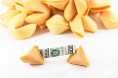 Chinese Fortune Cookie open wi. Chinese Fortune Cookie on top of heap, with money, cash neatly folded inside the snack, on white background, many behind, to show Stock Images
