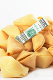 Chinese Fortune Cookie open wi. Chinese Fortune Cookie on a heap with money, cash neatly folded inside the snack, on white background, many behind, to show one Stock Photo