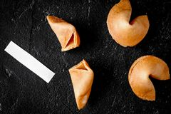Chinese fortune cookie with prediction on dark background top vi. Chinese fortune cookie with prediction on dark background close up top view royalty free stock image