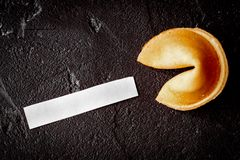 Chinese fortune cookie with prediction on dark background top vi. Chinese fortune cookie with prediction on dark background close up top view royalty free stock photo