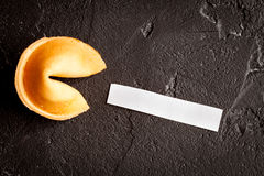 Chinese fortune cookie with prediction on dark background top view Royalty Free Stock Photography