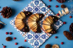 Chinese fortune cookies. Delicious traditional Fortune cookies on a blue background with Christmas decorations, close-up Royalty Free Stock Photo