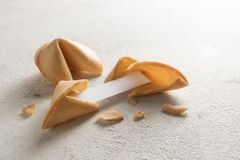 Chinese fortune cookies, one is cracked with blank paper slip for the prediction on a light background with copy space. Selected focus, narrow depth of field stock photos