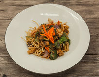 The Chinese fried noodles with squids, an octopus and vegetables. Stock Images