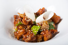 Chinese fried pork meat. Served on a white plate Royalty Free Stock Photography