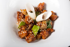 Chinese fried pork meat. Served on a white plate Stock Photo