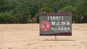 Chinese funny warning sign. On the beach closeup royalty free stock image