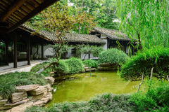 Chinese gallery by verdant pond of sunny summer afternoon Royalty Free Stock Photo