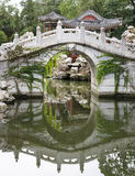 Chinese garden. White marble arch bridge with reflection and ancient pavilion in chinese garden Stock Photos