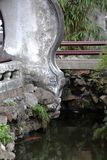 Chinese garden. Footbridge and concrete / stone balustrade or parapet above river with goldfish stock images