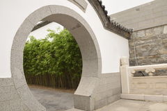 Chinese garden gate. The door to the Chinese garden, the elegant door, the white wall, in line with the Chinese people`s aesthetic standards of ancient culture Royalty Free Stock Photo
