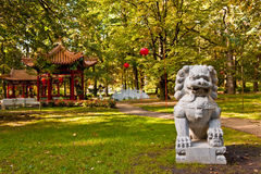 Chinese garden in Lazienki park (Royal Baths park), Warsaw. Chinese garden with pagoda pavilion, lanterns and guarding lion in Lazienk park (Royal Baths park) Stock Photo