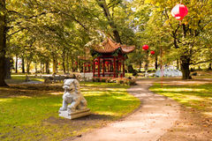 Chinese garden in Lazienki park (Royal Baths park), Warsaw. Chinese garden with pagoda pavilion, lanterns and guarding lion in Lazienk park (Royal Baths park) Stock Photos