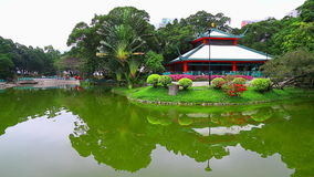 Chinese garden with pavilion and green pond stock footage