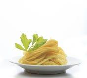 Chinese gele eierennoedel op witte schijf met groene bladeren van Ce Stock Fotografie