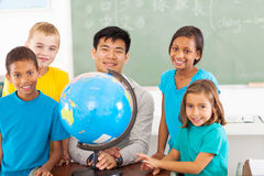 Chinese geography teacher. Cheerful primary school geography teacher and students with a globe Royalty Free Stock Images