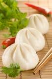Chinese gestoomde broodjes op de achtergrond van de bamboemat met koriander Royalty-vrije Stock Fotografie
