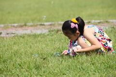 Chinese girl. The Chinese girl looking at the Bubble on the grassplot Stock Images