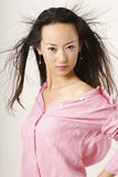 Chinese girl. Enticing Chinese girl with flying hair in pink shirt Stock Images